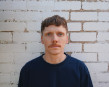 Rhys is depicted from the shoulders up against a white brick wall. He is wearing a black jumper a...